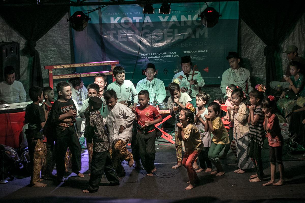 """Drama Anak Kapuk Teko pada """"Pentas Pendampingan Masyarakat Kapuk Teko"""" di kantor RW 01 Kapuk Teko, Cengkareng, Jakarta Barat, Selasa(30/12). Pentas Pendampingan Masyarakat Kapuk Teko merupakan presentasi hasil riset partisipatif tahap 1 kelompok Teater Kubur dengan warga Kapuk Teko  dalam program """"Kota yang Tenggelam"""". Program ini digagas komisi teater DKJ untuk mendalami berbagai sebab yang menimbulkan ancaman tenggelamnya  Jakarta."""